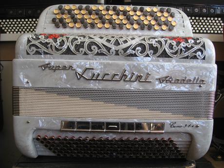 Accordeon Lucchini trois voix boite de resonance Peu connue sur notre territoire, la marque Lucchini, est une référence du genre. La ville de Stradella est dignement représentée par une autre fabrication: à travers Dallape. que l'on retrouve aussi assez fréquemment associée à l'étiquette Fratelli Crosio. Un regard suffit à la comparaison. L'instrument proposé aujourd'hui est bien le jumeau du Star six Crosio. A quelques nuances près. Du côté des basses offrant sept registres Anches type main Cagnoni clouées Cinquante deux notes six registres au pouce basson Do#2 à Mi6 en boite de résonance flutes Do#3 à Mi7 accordage swing Cent vingt basses sur cinq voix. Mi1 grave. Sept registres très gros son Accordé à neuf diapason 442Hz. Tous les accordéons vendus par Accord Deléon sont pourvus d'un jeu de bretelles housse ou étui neufs.