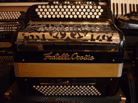 """Accordéon Fratelli Crosio compact boite de résonance Très rare dans ce type de format, particulièrement compact et muni d'une boite de résonance, cet accordéon sera le compagnon idéal pour le musicien nomade. Sa compacité lui confère une légèreté très appréciable. Il est parfait pour qui cherche à pratiquer les musiques de variété, bal, animations, spectacles de rue, et conviendra aussi parfaitement pour l'étude. Sa grille couvre notes en acier chromé offre un timbre remarquable, associant une excellente dynamique ainsi qu'un moelleux bien connus des amoureux des établissements Fratelli Crosio. Accordeon Fratelli Crosio compact boite de resonance A main droite Quarante six notes à main droite sur un clavier de quatre rangs de boutons dont le touché est exceptionnel. Sa tessiture va de Sol à Mi. Celui ci est constitué d'un jeu d'anches type main Cagnoni de très belle qualité, et d'un montage d'anches clouées sur cuir remarquable. Il possède cinq registres derrière le clavier et six sélecteurs pour la répétition des deux voix unisson:""""musette"""". A main gauche Quatre vingt seize basses sur quatre voix, il possède trois registres bien différenciés. Mécanique 3/3. Accordé au diapason 442Hz. Tous les accordéons vendus par Accord Deléon sont pourvus d'un jeu de bretelles housse ou étui neufs."""