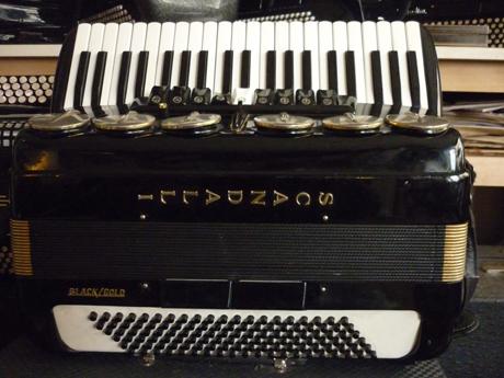 Accordéon Scandalli piano quatre voix Black Gold Les établissement Scandalli ont toujours été à la pointe de l'innovation en matière de fabrication des accordéon de très haute qualité. Leur production est remarquable sur toute l'étendue de sa gamme, aux composants de première bourre, installés par des ouvriers toujours conséquents. Ils on activement participé à la renommée de la marque Farfisa, associés à Settimio Soprani, dont les caractéristiques sont similaires. Cet accordéon possède l'option noir et or, significative de luxe, d'où son appellation BLACK GOLD. Les sommiers sont dans la pure tradition de l'artisanat d'art, aux bois remarquables, et bien vieillis, qui amplifient généreusement quatre voix d'anche tipo a mano, avec piccolo, fond plat. Il possède un basson, deux flutes et un piccolo. Les anches sont de type main, montées à la cire d'abeilles, les peaux d'anches sont en cuir. Les parties mécaniques exceptionnelles confèrent aux clavier un toucher d'une qualité tout aussi exceptionnelle. Les sourdines sur le couvre notes offrent la possibilité de modifier le timbre, en simulant l'effet boite de résonance, sans les inconvénients de poids ni de dimensions, et sur toutes les voix. Cet accordéon Scandalli piano quatre voix Black Gold est accordé au diapason 442 Hz, fera le bonheur du musicien comme de ses auditeurs. Il possède aujourd'hui un accordage musette, et il est possible d'en modifier la teneur, vers un brio plus discret, selon votre désir. Les parties mécanique constituant la main gauches sont dans la plus pure tradition des établissement Scandalli, elles de démontent en un instant, sans connaissance particulière, et permettent à tout un chacun de 'intervenir rapidement en cas de besoin. Mais un accordéon Scandalli ne tombe jamais en panne. cet accordéon Scandalli sera entièrement ré accordé après réfection intégrale des ses composants. Tous les accordéons vendus par Accord Deléon sont pourvus d'un jeu de bretelles housse ou étui neufs.