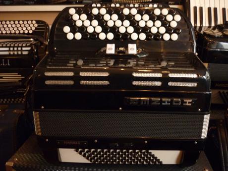 Accordeon etude Hohner Fortuna 2 deux voix. Peu connu dans cette marque, cet accordéon possède des qualités remarquables. Particulièrement compact et léger il permet de pratiquer l'étude, et pourquoi pas la scène. Les dimensions amples du clavier main droite permet un confort de jeu étonnant, et très peu usité dans cette catégorie. Cinq rangs de boutons, offrent la possibilité de moduler vers toutes les tonalités, ainsi que de jouer en accords très aisément. D'une grande dynamique, il offre une grande palette de nuances. Deux voix basson et flute. Trois registres. Tessiture de trente sept notes de Sol à Sol. Soixante douze basses sur quatre voix. Deux registres. Accordé au diapason 442Hz. Tous les accordéons vendus par Accord Deléon sont pourvus d'un jeu de bretelles housse ou étui neufs.