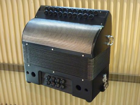 AXIOME accordéon diatonique fabrication Accord Deléon  AXIOME accordéon diatonique fabrication Accord Deléonest compact sobre atypique dynamique et magnifique, dont le timbre original est du àl'architecture de ses caisses. Un soin particulier à été dispensé afin de projeter le son vers l'avant: Le public. Son spectre sonore emplit tout l'espace, à la façon d'une enceinte. On le croirait amplifié. L'inclinaison des claviers offre une position idéale à la main, favorise le confort, entraine un jeu souple et dynamique. Les boutons de grand diamètre améliorent la virtuosité. AXIOME est réalisé grâce à des matériaux choisis avec rigueur, ainsi que l'ambition de vous offrir le meilleur de la facture artisanale. Caisses et sommiers sont dessinés réalisés et assemblés à l'atelier, ainsi que les parties mécaniques en acier. Les soupapes bois et feutre sont particulièrement silencieuses, et offrent une excellente compression. Une grille couvre notes en acier doux, et inoxydable, (les deux options sont offertes), lui confère un mordant sans pareil dans la facture traditionnelle des accordéons diatoniques construits de façon artisanale. Des jeux d' anches faits à la main permettent à cet accordéon de sonner haut et fort. Et loin! Ils sont fixées à la cire d'abeilles, sur des sommiers en epicea, afin d'alléger l'instrument et améliorer la résonance. Les attaquent claquent, les forte sont ahurissants, et les jeux en pianissimi sont d'une douceur remarquable. Que du bon. Deux voix flute à main droite, pour vingt et une touches, sur deux rangs, les altérations sont en bout du clavier. Huit basses sur quatre voix offrent une sonorité incomparable dans cette catégorie d'instrument. Trois voix pour les basses, une voix aux accords. AXIOME est disponible dans la tonalité de votre choix, livré avec bretelles et courroie en velours large. Une housse souple de très belle facture en assure la protection. A écouter voir.