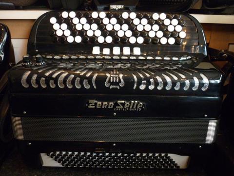 Accordeon ZeroSette Trois voix cent vingt basses Zero Sette nous offre un catalogue impressionnant d'instruments de toute première qualité, tant pour les amateurs éclairés que pour les professionnels. Le son authentique depuis 1945. La marque est reconnue dés sa création en 1945, et conquière immédiatement les marchés Européens, les USA, l'Asie et l'Australie. Idéal pour l'étude, voire le jeu professionnel, cet accordéon Zero Sette possède trois voix au chant, composées de deux flutes, et un basson. Il ne possède pas de boite de résonance, ce qui le rend plus léger. malgré cette absence, la voix basson sonne très profondément, avec un contenu harmonique des plus séduisant. Les sommiers sont d'excellente qualité, bien taillés, et offrant une très large plage dynamique. Les anches sont de type main, montées à la cire, les peaux d'anches sont en cuir. Le clavier chant type international est équipé de boutons larges. Ceci permet un jeu plus fluide. Agrémenté de cinq rangs de boutons, il offre quarante six notes de Mi à DO# sur deux rangs de soupapes. Nous avons ici un accordéon de type caisse piano, un peu plus haut et nettement moins large. Ceci améliore la position de jeu, et modifie le timbre de l'instrument. du reste, il semble plus léger. Il possède cinq registres devant le clavier, aisément accessibles. Côté main gauche. Cent vingt basses occupent un clavier de type 2/4, avec deux rangs de basses, et quatre rangées aux accords, sont inclus les accords diminués si propices aux accords de passage en cas de modulation. Cinq voix de basses offrent un beaux spectre sonore, la note la plus grave est un LA. Il est doté de deux registres sur trois sélecteurs. Ceci offre cinq voix, ou trois. Cet instrument sera accordé selon votre désir, toutefois, il est préférable de lui garder une vibration modérée, voire très lente, genre swing. Il est idéal pour pratiquer un son»jazz». A noter l'apparence particulièrement propre, de cet accordéon, comme neuf. Tous les accordéons vendu