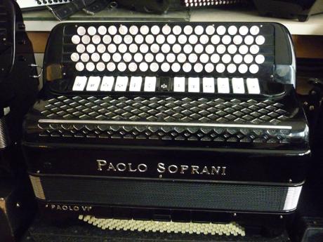 Accordeon Paolo Soprani quatre voix piccolo cent vingt basses Voici une superbe réalisation des ouvriers de chez Paolo Soprani. Ce modèle est extrêmement rare dans sa palette sonore, comme dans sa réalisation. Les matériaux le constituant sont de toute première qualité, l'assemblage est à l'avenant, moyennant quoi il chante dans toutes les nuances du spectre. Haut et fort. Les caisses sont de type piano, quarante huit centimètres par vingt, sur deux rangées de soupapes. La tessiture main droite est de quarante six notes de Mi à DO#, sur quatre voix, 16 8 8 4, basson deux flutes piccolo. Il comporte treize registres devant un clavier de type international sur cinq rangs, pour une largeur de voie de vingt millimètres. La table d'harmonie ne comporte pas de boite de résonance, ce qui en facilite l'amplification. Cet accordéon de qualité professionnelle affrontera la scène avec morgue et faconde, pour le plus grand bonheur du musicien, ainsi que de son auditoire. A noter l'état cosmétique exceptionnel, des caisses, exemptes de traces ou rayures. L'accordage est complet, incluant le changement intégral des peaux, le diapason est à 442 Hz. Le brio est aujourd'hui musette, il est possible de le modifier. La caisse des basses comporte sept registres, et cinq voix, la note grave est LA. Le sommier des grosses basses est coudé afin d'en améliorer le volume et la profondeur de note, les anches sont de type main de la grand époque, rivalisant allègrement avec les fabrications actuelles. La mécanique en fil d'acier comporte deux rangées aux basses, quatre rangées aux accords, avec les accords septième diminués. A venir écouter voir. Tous les accordéons vendus par Accord Deléon sont accordés à neuf. Pourvus d'un jeu de bretelles housse ou étui neufs. Assortis d'un service après vente offrant garantie et qualité