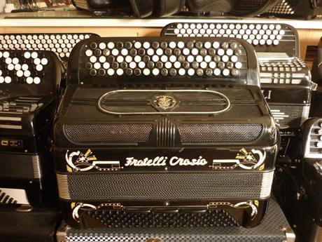 Accordéon occasion Fratelli Crosio trois voix boite de résonance Fabriqué dans les années soixante, par les établissements Dallape situés à Stradella, et distribué par Fratelli Crosio, cet accordéon possède un niveau de fabrication étonnant que et. Un état de conservation rarissime, séduira les musiciens les plus exigeants, amoureux du son de la grande époque, il est pour vous. Il offre une excellente compression, et est entièrement raccordé à l'état du neuf. Les peaux d'anches ont été changées dans leur intégralité. les anches de marque Carloni type main en acier inoxydable sont remises à neuf avant accordage complet au diapason 442Hz. Le soufflet est remis à neuf. Tout est neuf. Les voix flutes accordées américain, offrent un timbre fin et puissant. Ça sonne à tous les étages. Le basson en boite de résonance possède une profondeur inégalée par rapport aux fabrications actuelles. Celle ci est en aluminium brossé, typique des fabrications Dallape. On peut « pitcher » (descendre la hauteur du timbre) de façon incroyable, gage de reconnaissance d'un excellent montage associé à jeu d'anches de qualité équivalente. Voici l'accordéon Idéal pour approcher le son jazz. Les anches sont montées sur cuir et clouées. Accordéon Fratelli Crosio trois voix boite de résonance A main droite Cinq rangées de boutons noirs et blancs afin de mieux se repérer. Six registres derrière le clavier, avec répétition de la voix « musette » aux extrémités. A main gauche Quatre voix de basses avec Mi grave. Trois registres bien différenciés. Les poussoirs de la mécanique sont en inox ce qui amplifie le son, en libérant de l'espace dans la caisse. Et cela s'entend. Mécanique munie de deux rangées de basses et quatre rangées aux accords, incluant les accords septième diminués. La basse chante comme un orgue Hammond, comme un ampli à lampes! Ça gratte. A venir écouter voir. Tous les accordéons vendus par Accord Deléon sont accordés à neuf, selon votre désir. Pas révisés, accordés à neuf. Et pourvus