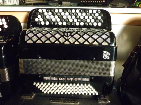 Accordéon convertisseur Ballone Burini Aria 43B Idéal pour le second degré d'étude du conservatoire, cet accordéon muni d'un convertisseur de basses chromatiques enchantera nos étudiants adolescents comme adultes. Compact et léger, dimensions: 38 x 21cm d'un poids de 8,8 Kg, il permet une grande palette de nuances, ainsi qu'un volume sonore inégalé. Les composants qui le remplissent sont à la hauteur de la réputation de qualité inhérente la marque. La caisse est recouverte de celluloid, plus solide que la peinture. A main droite Le clavier chant comporte quarante six notes réparties sur cinq rangs, pour un total de soixante seize boutons. La tessiture va de DO# à DO#. Il possède deux voix, basson et flute, 16 et 8, et offre trois registres en mentonnières. A main gauche. Six rangs de boutons et une mécanique 2/4, pour deux rangées de basses, et quatre aux accords, incluant les accords septième diminués. Un clavier de quatre vingt seize boutons. Trois registres en mode standard, autant en mode convertisseur. IL comporte quarante notes en mode basses chromatiques, sur quatre rangs. Tessiture: La à DO et deux voix, basson et flute. 16 et 8. Cet accordéon d'occasion d'apparence neuve, à été entièrement accordé à l'atelier avant cession. Diapason 442Hz. Il est délivré avec un étui dur, ainsi que d'une paire de bretelles neuves. Assortis d'un service après vente offrant garantie et qualité.